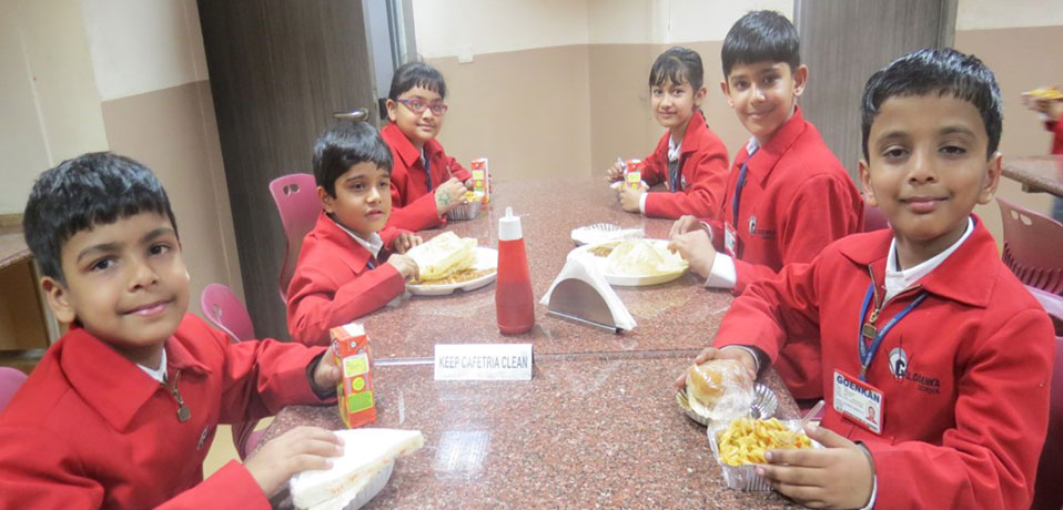 school with cafeteria,student of junior wing having their meal in cafeteria