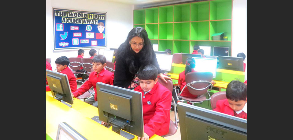 best private school in rohini,a teacher teaching the students in computer lab