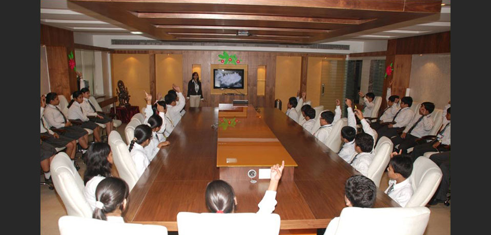 the image shows students of secondary wing taking part in conference,school with conference hall