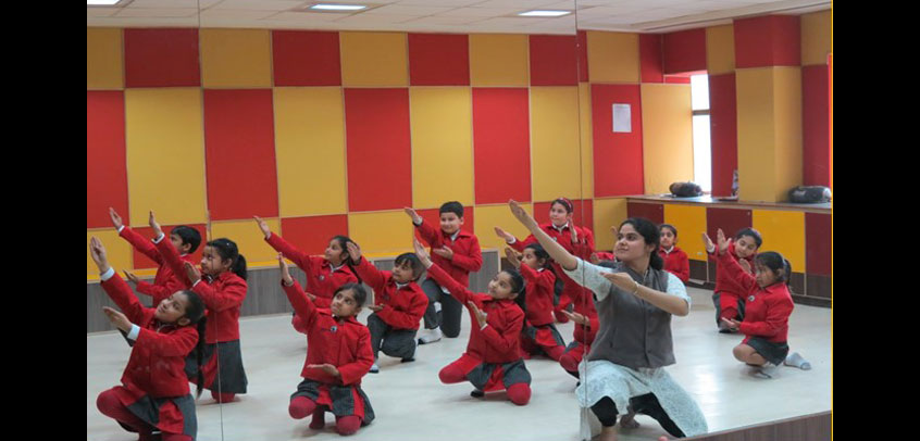 the image shows teacher teaching dance to girl students,school with theatre