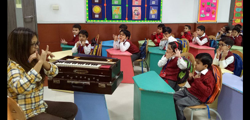 top school in extra curricular activities, students of junior wing learning music lessons from their teacher