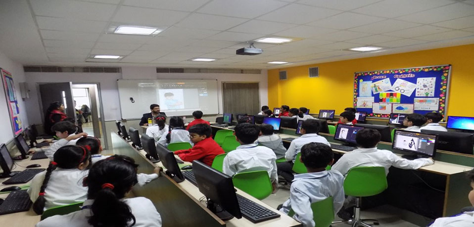 the image shows the students are studying in computer lab,school with smart class